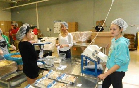 Students volunteer to work at Feed My Starving Children's mobile program.