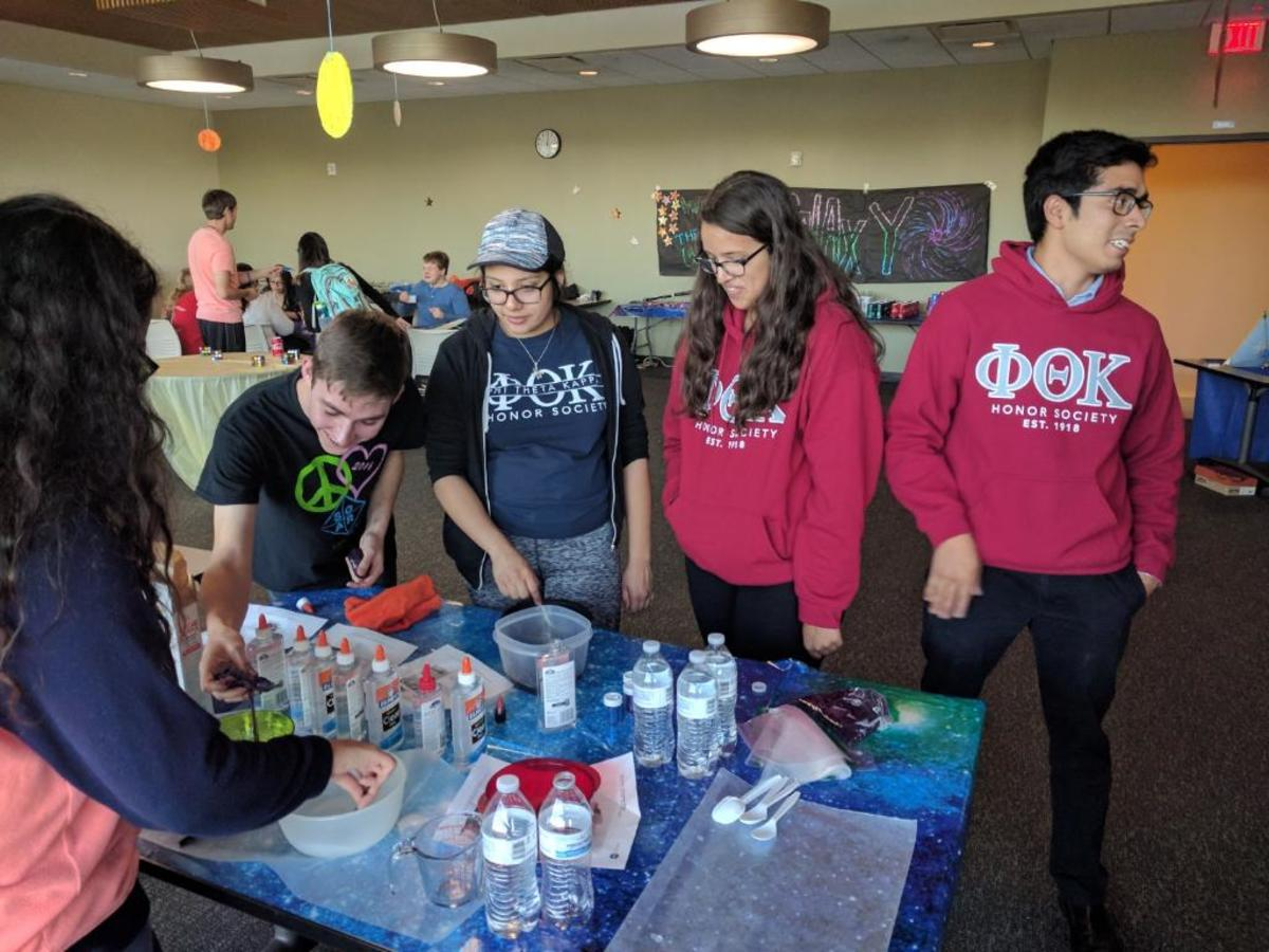 Members of Phi Theta Kappa help students with NASA themed activities at