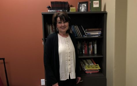 English Professor, Rachael Stewart, poses in front of the many bookshelves in her office.