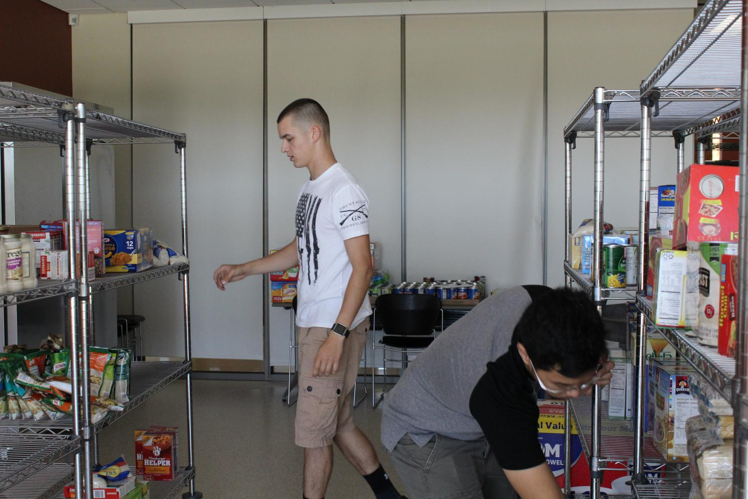 Jackson Wozniak, the Chair of PTK's Vice President (left), and Emilio Edemni, Food Pantry co-officer (right) were reorganizing the food pantry that was recently expanded