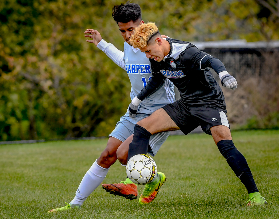 Aldo Lazaro attempts to maintain control of the ball during the Region 4 Championship game against Harper College