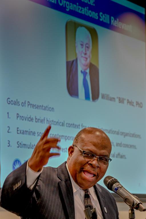 ECC+President+David+Sam+highlights+a+point+as+the+image+of+Dr+Pelz+smiles.