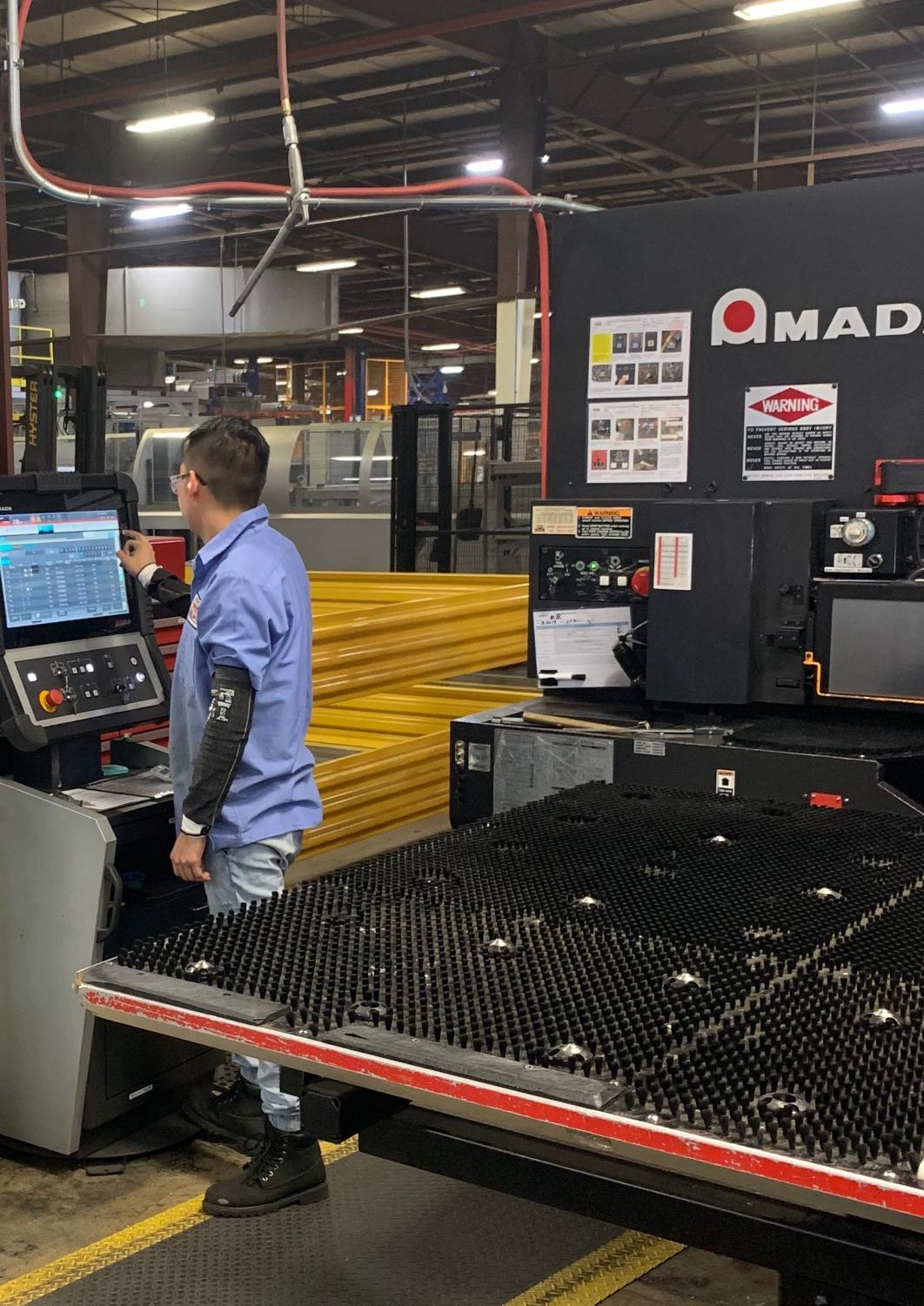 Late into his shift, first-year student Fausto Gallardo is seen programming his machine at the KNAACK manufacturing plant in Crystal Lake, Illinois.