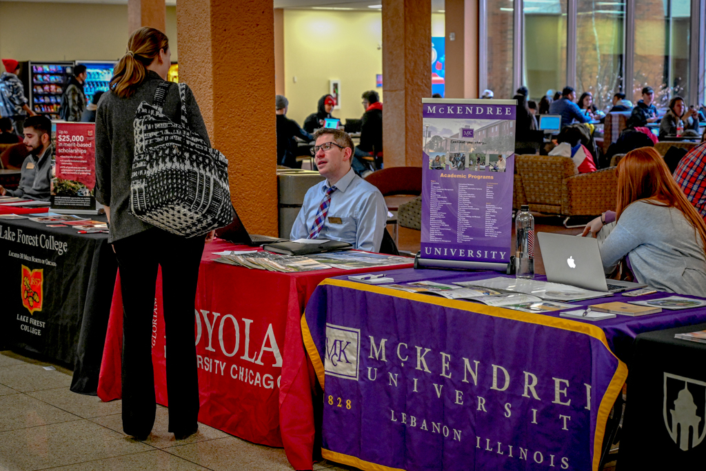 Loyola university recruiter engages student in discussion of Loyola University's benefits.