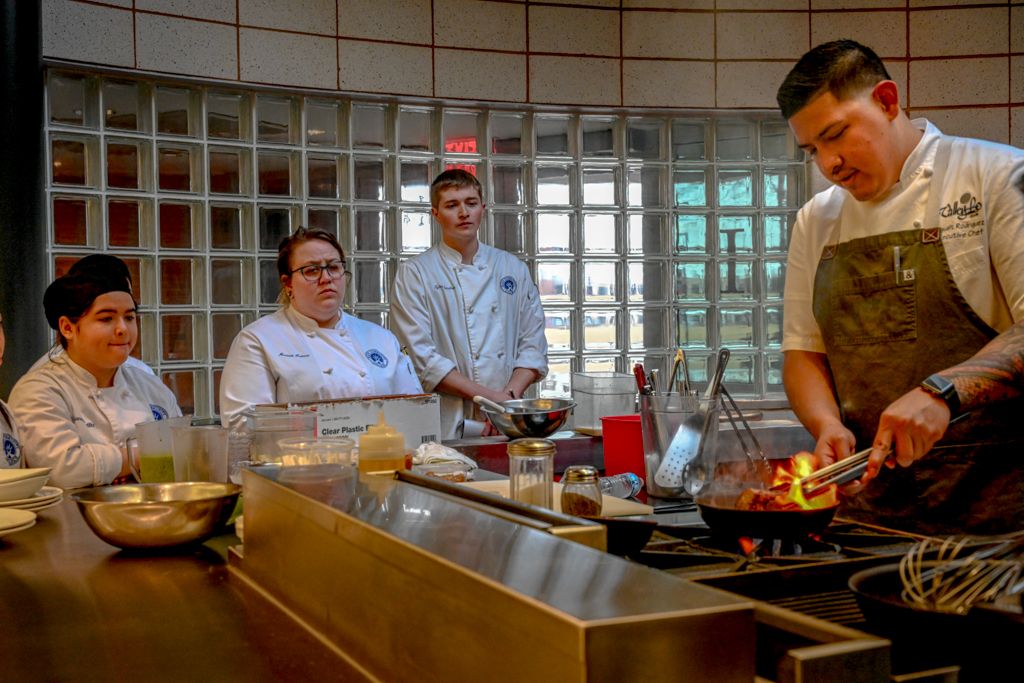 First-year ECC culinary students Adrianna Moffitt, Marissa Krause and second-year Tyler Jacobson watch intently as ECC grad and chef Josuelt Rodriguez sears a lamb roast. ECC hosted the spring 2019 visiting chef program and dinner in the Spartan Terrace Restaurant.